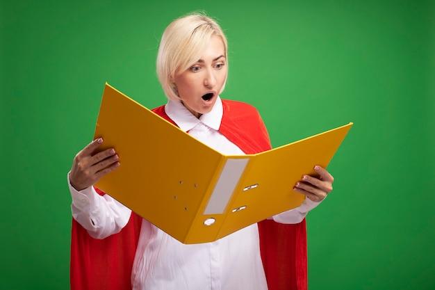 Verrast blonde superheld vrouw van middelbare leeftijd in rode cape houden en kijken naar map geïsoleerd op groene muur