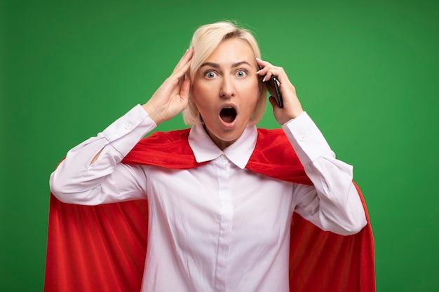 Verrast blonde superheld vrouw van middelbare leeftijd in rode cape met mobiele telefoon die hand op het hoofd houdt en het hoofd aanraakt met telefoon geïsoleerd op groene muur