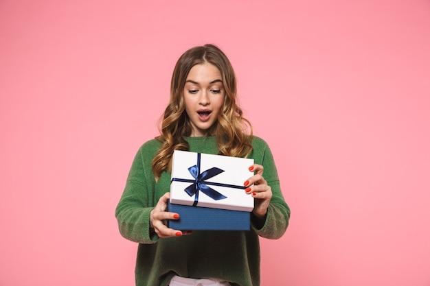 Verrast blonde vrouw draagt een groene trui die een geschenkdoos opent over roze muur