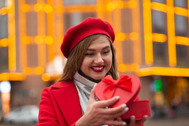 Verrast blonde vrouw draagt een rode baret en jas die een hartvormige geschenkdoos opent op de achtergrond van bokehlichten. ruimte voor tekst