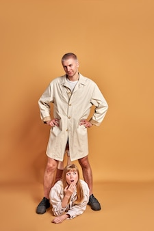 Verrast blonde vrouw liggen onder de voeten van geïsoleerde man, portret van jonge kerel in jas poseren