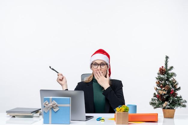 Verrast blonde vrouw met een kerstman hoed zittend aan een tafel met een kerstboom en een cadeau erop op witte achtergrond