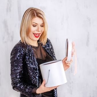 Verrast blonde vrouw opent een geschenkdoos