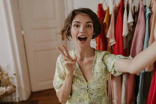 Verrast brunette krullend kortharige vrouw in zomer bloemenjurk neemt selfie, kijkt verrast en toont vredesteken in kleedkamer dressing