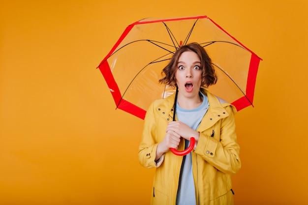Verrast brunette meisje draagt trendy lichte vacht poseren met open mond. binnenfoto van geschokte dame die met golvend haar rode parasol op gele muur houdt.