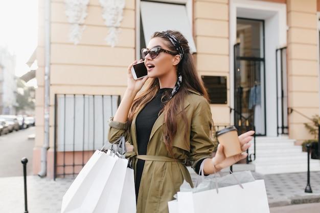 Verrast brunette vrouw praten over de telefoon op straat in herfst ochtend