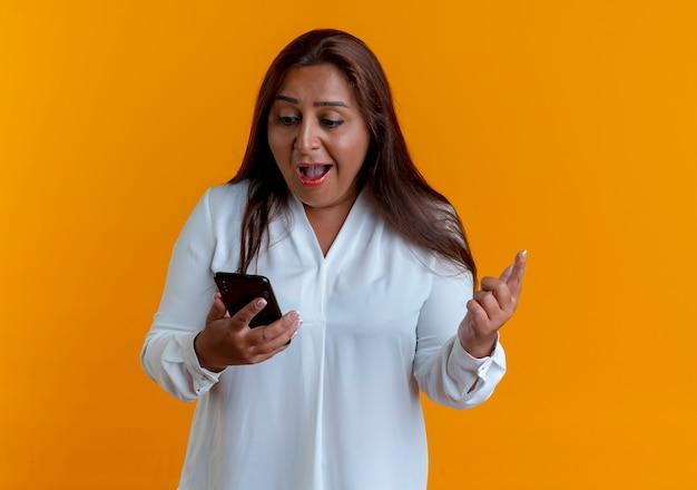 Verrast casual blanke vrouw van middelbare leeftijd houden en kijken naar telefoon geïsoleerd op gele muur