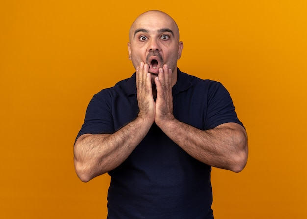 Verrast, casual man van middelbare leeftijd die de handen op de kin houdt en naar de voorkant kijkt geïsoleerd op een oranje muur
