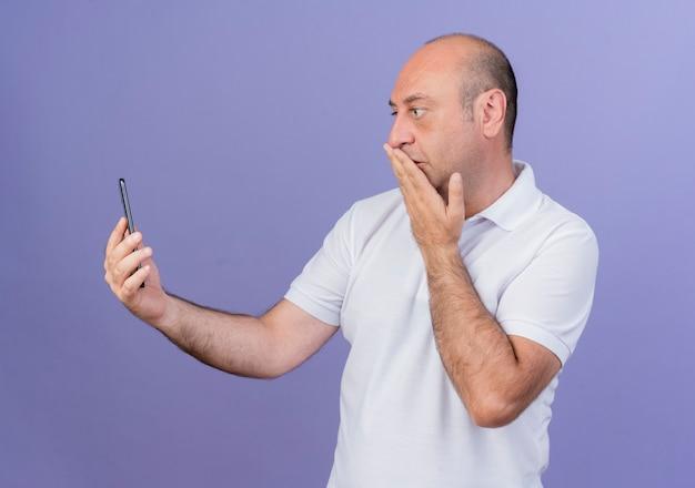 Verrast casual volwassen zakenman houden en kijken naar mobiele telefoon en hand zetten mond geïsoleerd op paarse achtergrond