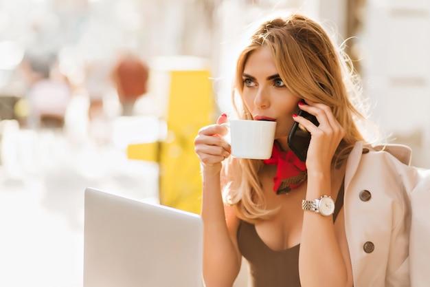 Verrast charmant meisje warme drank drinken en luisteren vriend op telefoon