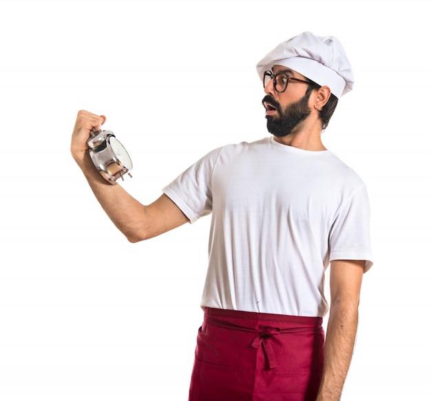 Verrast chef-kok met een klok over witte achtergrond