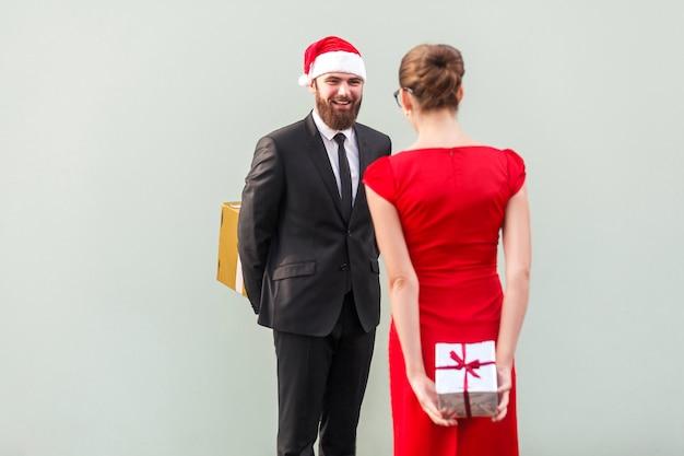 Verrast concept geluksvrienden die elkaar staan en een geschenkdoos achter de ruggengraat houden