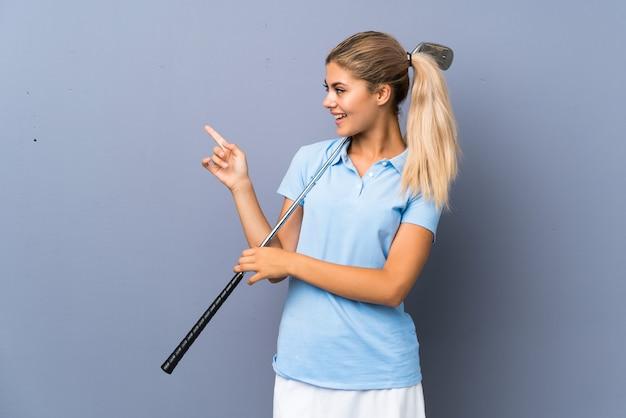 Verrast de golfspelermeisje van de tiener over grijze muur en het richten van vinger aan de kant