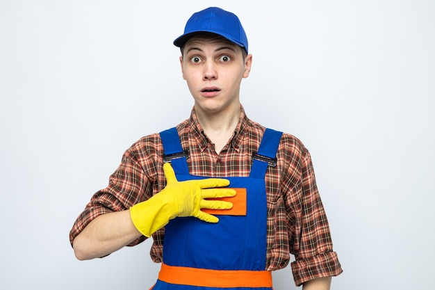 Verrast die hand op zichzelf legt, jonge schoonmaakster die uniform en pet met handschoenen draagt
