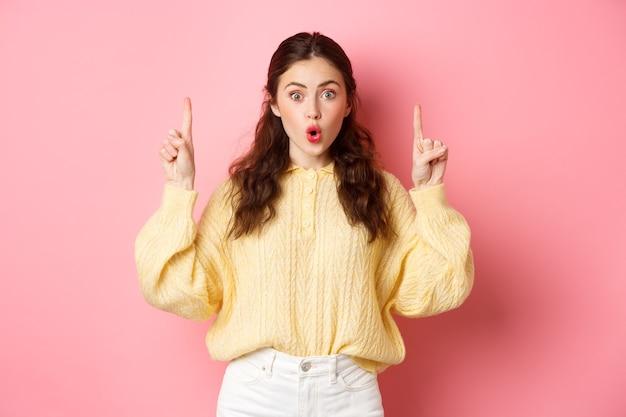 Verrast donkerbruin meisje hijgend verbaasd, zegt wow en starend naar de camera onder de indruk, wijzende vingers omhoog naar copyspace, staande tegen roze muur.