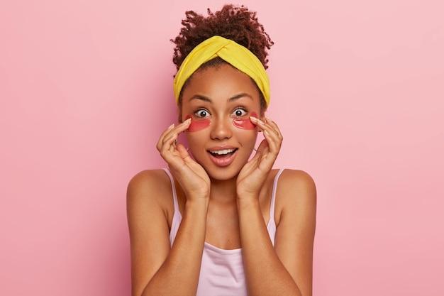 Verrast donkerhuidige, gekrulde jonge vrouw met collageenvlekken onder de ogen, ziet er indrukwekkend uit, vraagt zich af een geweldig verjongend effect van een schoonheidsproduct, draagt een gele hoofdband en een t-shirt.