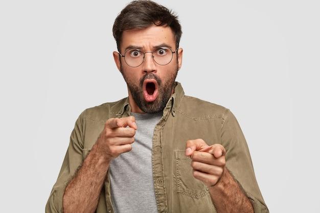 Verrast doodsbang ongeschoren jonge man heeft borstelharen met beide wijsvingers direct, kiest iets met shock, gekleed in modieus shirt, geïsoleerd over witte muur
