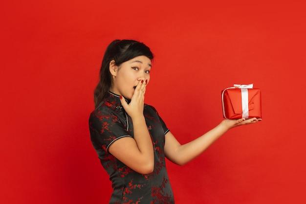 Verrast door cadeau. gelukkig chinees nieuwjaar 2020. het portret van het aziatische jonge meisje dat op rode achtergrond wordt geïsoleerd. vrouwelijk model in traditionele kleding ziet er gelukkig uit. viering, vakantie, emoties. copyspace.
