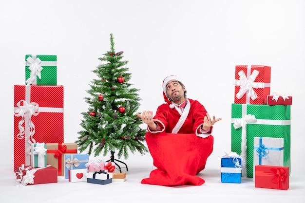 Verrast emotionele opgewonden verward jonge volwassene verkleed als kerstman met geschenken en versierde kerstboom zittend op de grond op witte achtergrond