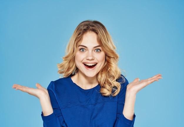 Verrast emotionele vrouw in blauwe jurk gebaren met hand blauwe achtergrond