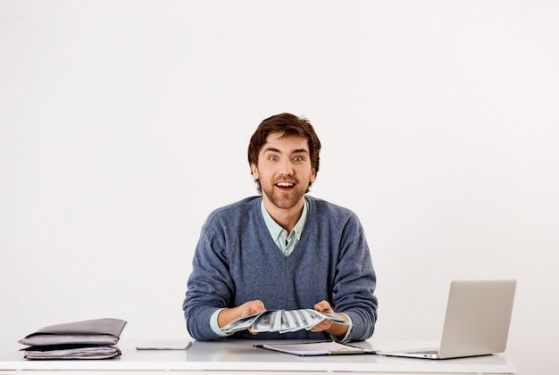 Verrast en blij, opgewonden jonge zakenman, verdiende eerste inkomen uit zaken, contant geld vasthouden, geld tellen en glimlachen