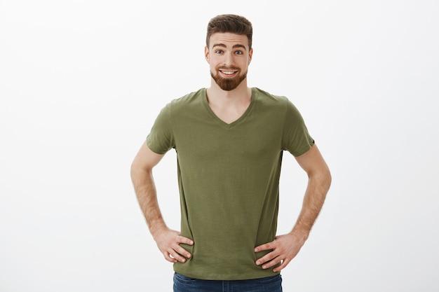 Verrast en enthousiaste knappe atletische bebaarde man in t-shirt hand in hand op de heupen en glimlachend wenkbrauwen optrekken van amusement en verbazing poseren ontspannen over witte muur