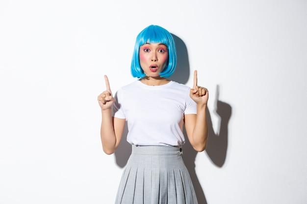 Verrast en gefascineerd aziatisch meisje in blauwe korte pruik, kawaii make-up, kijkt onder de indruk en wijst met de vingers omhoog, toont logo of promobanner, staand.