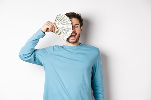 Verrast en gelukkig jongeman die de helft van het gezicht bedekt met geld, hijgend verbaasd naar de camera, snelle leningaanbiedingen bekijkt, staande op een witte achtergrond.