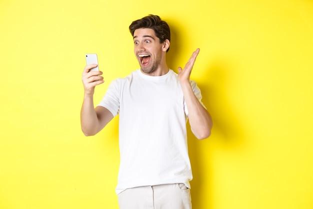 Verrast en gelukkig man kijken naar het scherm van de mobiele telefoon, fantastisch nieuws lezen, staande op gele achtergrond.