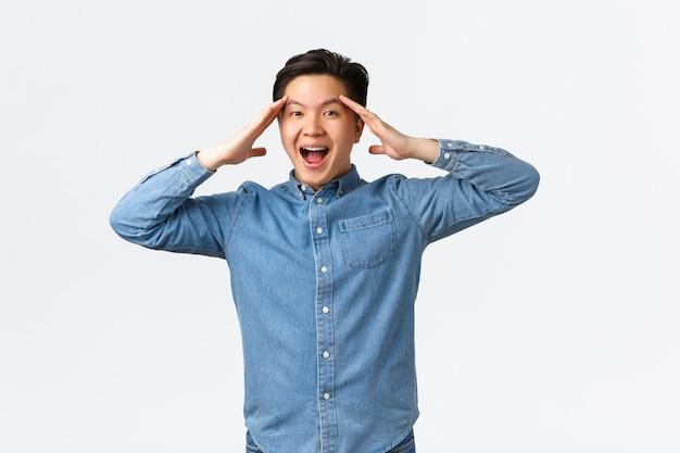 Verrast en gelukkig, opgeluchte aziatische man die zich verheugt over geweldig nieuws, handen in de buurt van het hoofd houdt en vrolijk glimlacht, probleem heeft opgelost, zich vrolijk en vrolijk voelt op een witte achtergrond.