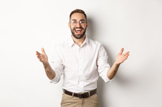 Verrast en gelukkig zakenman heet u welkom, kijkt opgewonden en glimlachend, staande tegen een witte achtergrond.
