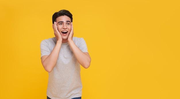 Verrast en geschokt aziatische man die mond bedekt met handen geïsoleerd op felgele achtergrond.