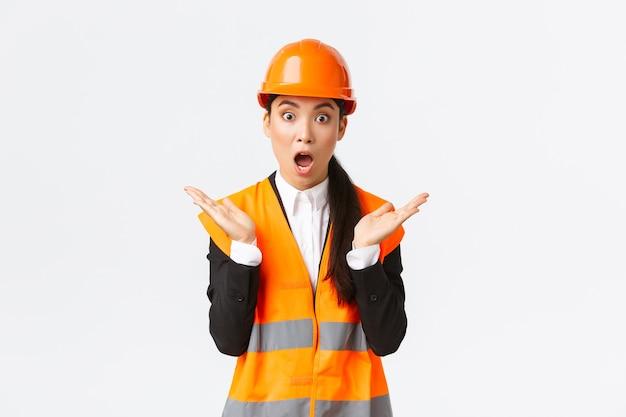 Verrast en geschokt aziatische vrouwelijke ingenieur in reflecterend jasje, veiligheidshelm, reageren op onverwacht nieuws, handen opsteken en klappen onder de indruk, bezoek bouwgebied, blij met geweldig werk