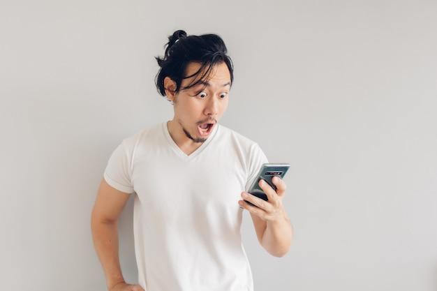 Verrast en geschokt lang haar man in wit t-shirt gebruikt smartphone.