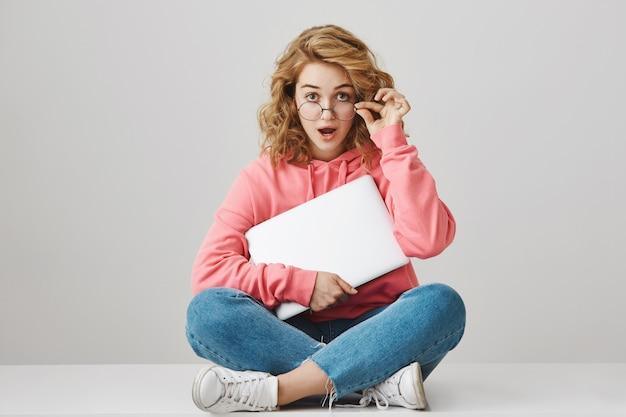 Verrast en geschokt meisje opstijgen bril, zittend met laptop op de vloer