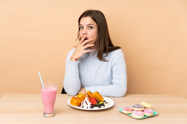 Verrast en geschokt tienermeisje die wafels op beige eten terwijl net het kijken