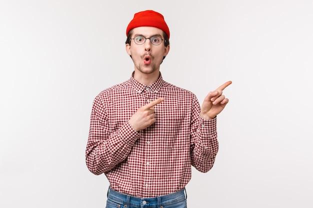 Verrast en nieuwsgierig grappige bebaarde man in rode muts, bril vouwen lippen van verbazing en interesse vragen stellen over cool nieuw product op voorraad, wijzend rechtsboven