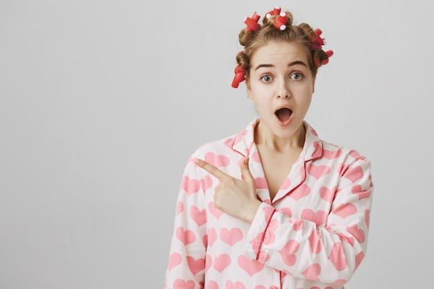 Verrast en nieuwsgierig schattig meisje in nachtkleding en haarkrulspelden wijzende vinger naar links op banner