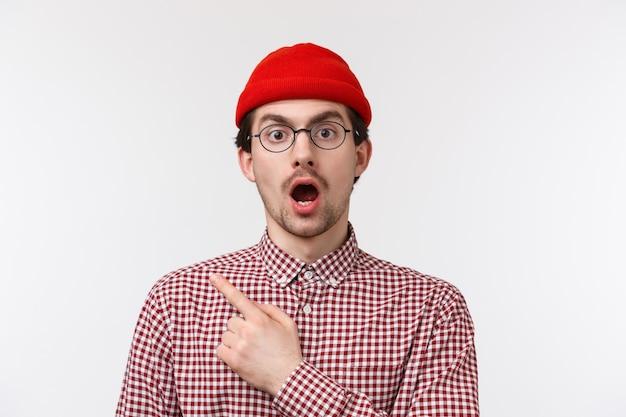 Verrast en onder de indruk knappe bebaarde hipster-man in bril en rode muts, open mond en neergeslagen kaak verbluft, zag iets schokkends, wees naar de linkerbovenhoek,