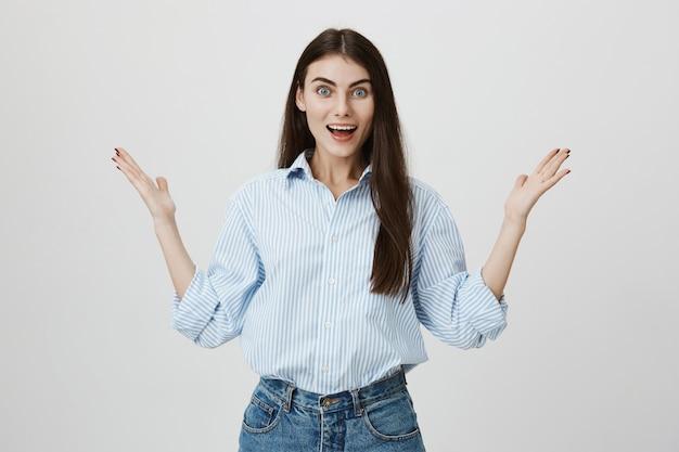 Verrast en opgelucht vrouw handen opsteken, glimlachend