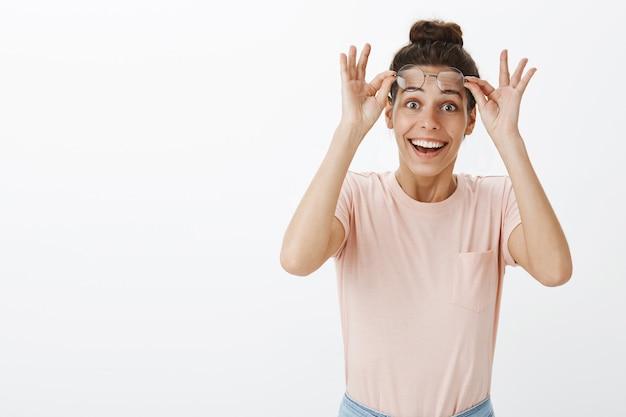 Verrast en opgewonden meisje met bril poseren tegen de witte muur