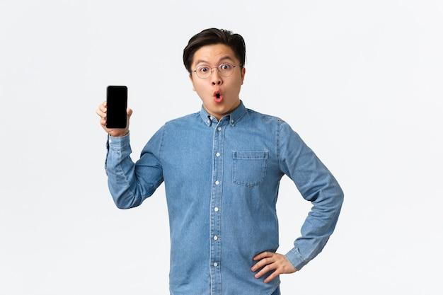 Verrast en verbaasd aziatische man in bril en vrijetijdskleding, mobiele telefoon scherm tonen en wow zeggen, bespreken nieuwe smartphone applicatie, laatste nieuws online, witte achtergrond
