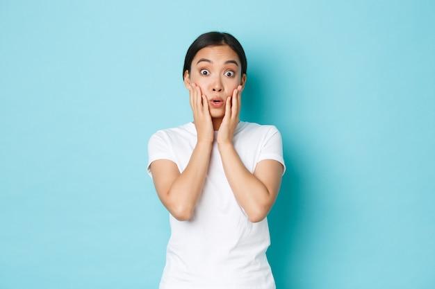 Verrast en verbaasd aziatische studente reageert op geweldig nieuws, kijkt onder de indruk, hijgt naar adem en zegt wow onder de indruk, staande lichtblauwe muur verbaasd