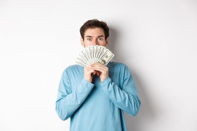 Verrast en verbaasd knappe kerel die geld toont, promo-aanbieding bekijkt, met contant geld gaat winkelen, die zich over witte achtergrond bevindt.