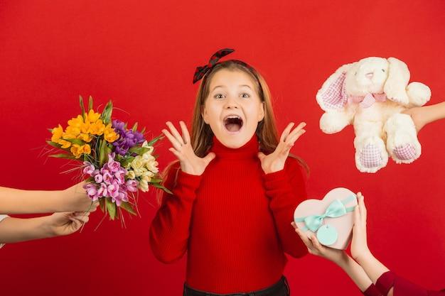 Verrast en verbaasd meisje dat veel cadeautjes ontvangt voor valentijnsdag