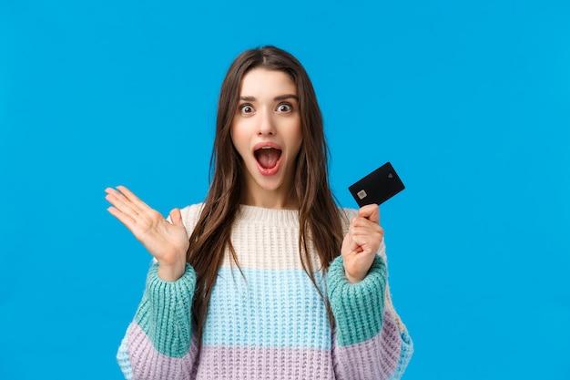 Verrast en verbaasd meisje ontving bonus op bankrekening, hand opgestoken met creditcard, schreeuwend van verbazing en geluk, kreeg veel geld, verspilde sparen voor vakantiegeschenken, blauwe achtergrond
