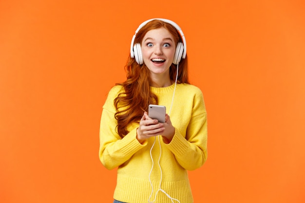 Verrast en verbaasd, opgewonden glimlachende roodharige vrouw ontdekte dat hun favoriete band een nieuw nummer heeft uitgebracht