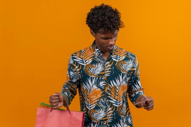 Verrast en verward jonge knappe donkere man met krullend haar in bladeren bedrukt overhemd met boodschappentassen en vreemd naar een creditcard kijken terwijl hij op een oranje achtergrond staat