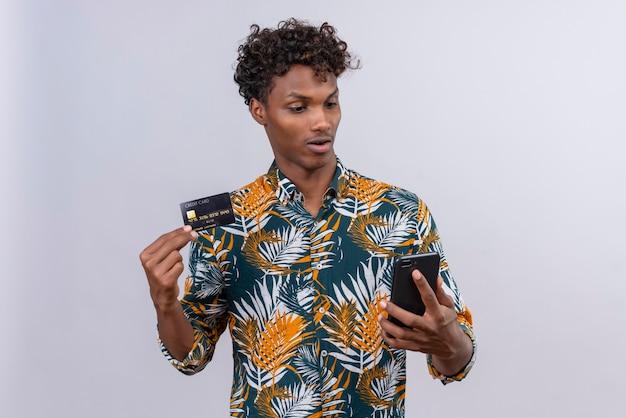 Verrast en verward knappe donkere man met krullend haar creditcard tonen terwijl hij naar mobiele telefoon kijkt op een witte achtergrond