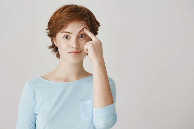 Verrast en verwonderd roodharig meisje dat tegen de witte muur poseert